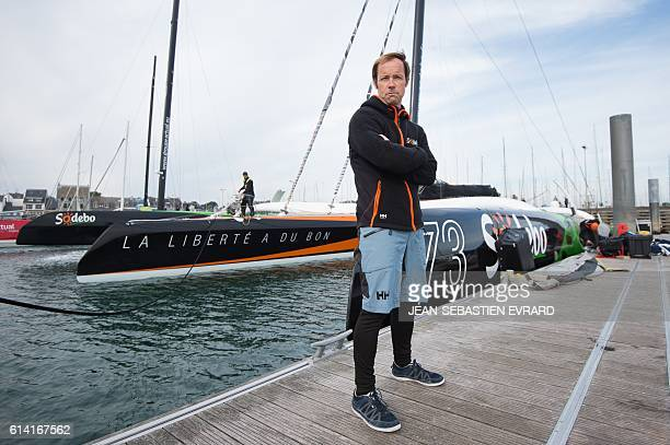French skipper Thomas Coville poses infront his multihull 'Sodebo Ultim' on October 12 2016 at La TrinitesurMer western France Coville prepares for a...