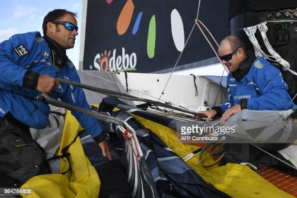 French skippers Thomas Coville and JeanLuc Nelias prepare the 'Sodebo' Ultim multihull prior to sailing during a training session off the coast of La...
