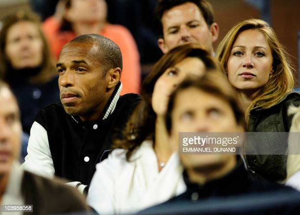 French soccer player Thierry Henry sits with his girlfriend Andrea Rajacic to watch the match between Swiss tennis player Roger Federer and Swedish...