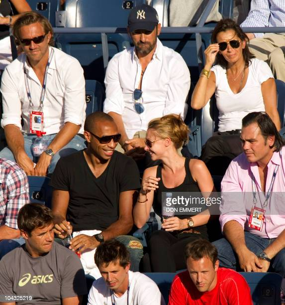 French soccer player Thierry Henry sits with his girlfriend Andrea Rajacic and watches the match between number three seeded Novak Djokovic of Serbia...