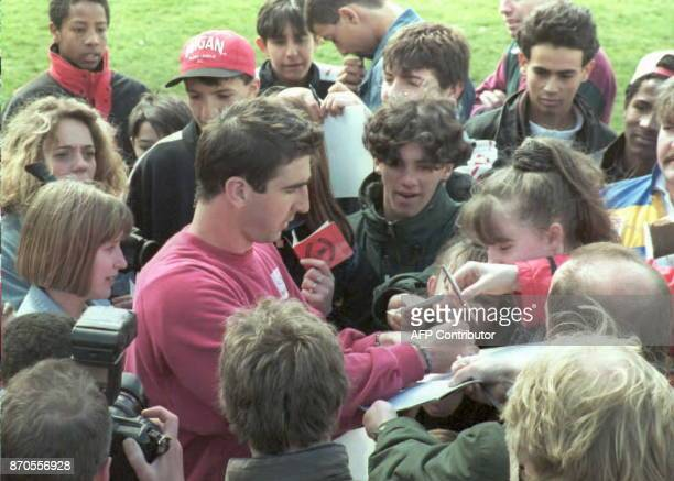 French soccer star Eric Cantona signs autographs for youngsters from a team from SouthWest France who watched their hero train with the reserves...