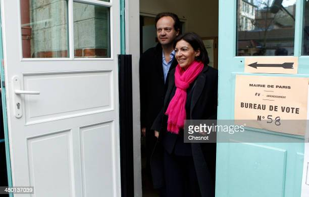 French Socialist party candidate for the Paris municipal elections Anne Hidalgo leaves a polling station with her husband JeanMarc Germain after...