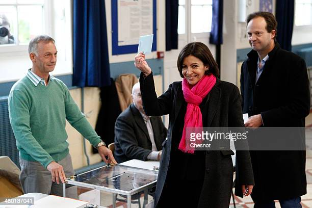 French Socialist party candidate for the Paris municipal elections Anne Hidalgo poses next to her husband JeanMarc Germain before casting her ballot...