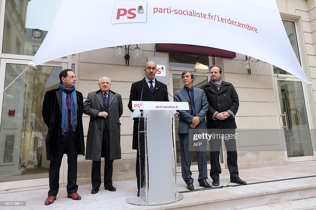 French Socialist Party (PS) First Secretary Harlem Desir (C) delivers a speech next to Ile-de-France regional counsellor Jean-Luc Romero (L), French entrepreneur and co-founder of the Yves Saint Laurent designer house Pierre Berger (2nd L), PS spokesman and MP David Assouline (2nd R) and PS MP Jean-Marc Germain (R) as they inaugurate a red ribbon on the facade of the PS headquarters in Paris on November 30, 2012 to mark the upcoming World AIDS Day on December 1. AFP PHOTO / THOMAS SAMSON