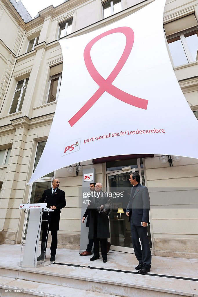 French Socialist Party (PS) First Secretary Harlem Desir (L), Ile-de-France regional counsellor Jean-Luc Romero (2nd L), French entrepreneur and co-founder of the Yves Saint Laurent designer house Pierre Berger (2nd R) and PS spokesman and MP David Assouline inaugurate a red ribbon on the facade of the PS headquarters in Paris on November 30, 2012 to mark the upcoming World AIDS Day on December 1.
