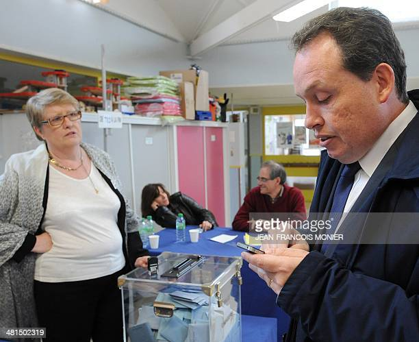 French Socialist Party mayor of Angers and candidate for his reelection Frederic Beatse visits a polling station and calculates on his phone the...