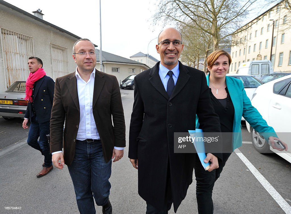 French Socialist Party (PS) national secretary Harlem Desir (C) arrives, surrounded by the PS Haute Vienne first secretary Laurent Lafaye (C,L) and PS national secretary in charge of memberships, Elsa Dimeo to attend a meeting with PS militants on April 5, 2013 in Limoges, central France.