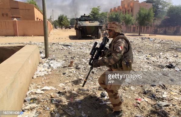 A French soldier and a light armored vehicle are pictured in a street as they fight while clashes erupted in the city of Gao on February 21 2013 and...
