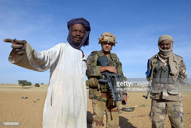 French soldier and Malian interpreter talk with a nomad as they control his camp on October 30 in a desert near the village of Bamba between Timbuktu...