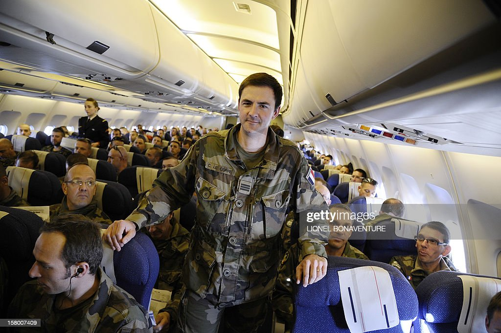 French soldier, captain Christophe Le Corre poses in the isle during flight beside French soldiers on a plane bound for France, on December 8, 2012 after leaving Paphos airport in Cyprus. Le Drian today welcomed some 150 French soldiers returning from Afghanistan. AFP PHOTO / LIONEL BONAVENTURE
