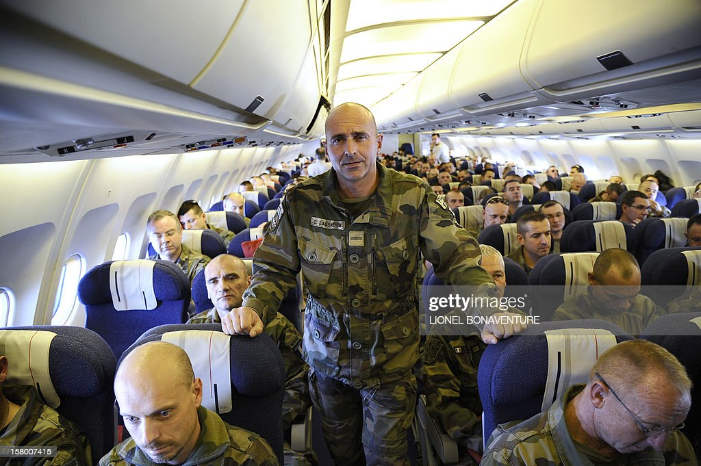 French soldier Celestin Lassauce poses in the isle during flight beside French soldiers on a plane bound for France, on December 8, 2012 after leaving Paphos airport in Cyprus. Le Drian today welcomed some 150 French soldiers returning from Afghanistan.