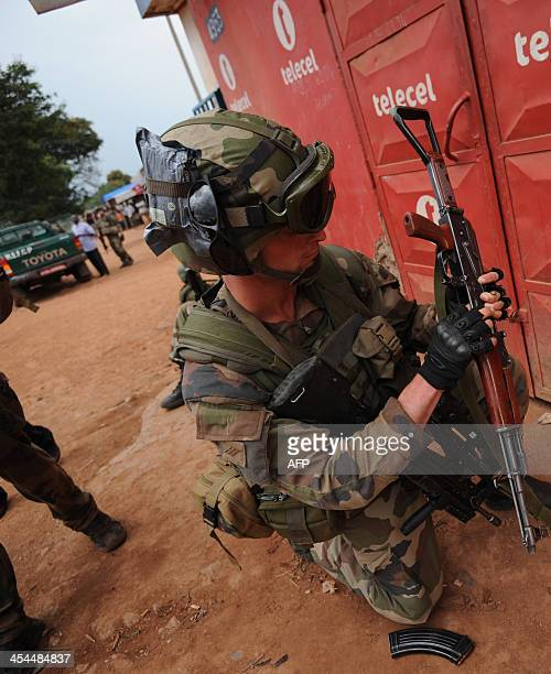 A French soldier checks a weapon taken from exseleka rebels in Bangui on December 9 2013 French troops on Monday began disarming fighters in the...
