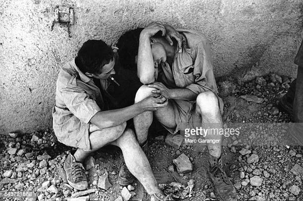 A French soldier comforts a comrade during Pere Cent the 100th day before the liberation of Algeria