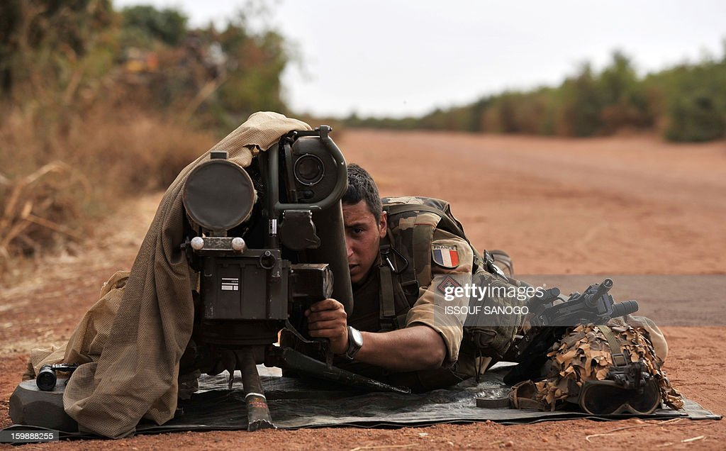 A French soldier deployed in Diabaly lays with a Milan anti-tank missile launcher at the forward posiotion near Diabaly on January 22, 2013. Italy said Tuesday it will send three planes to Mali to help support French and Malian troops battling Islamist rebels after parliament gave the green light for a two- to three-month logistical mission. AFP PHOTO / ISSOUF