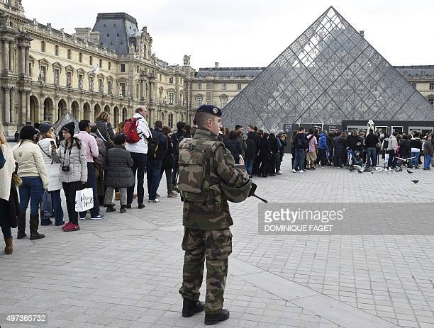 A French soldier enforcing the Vigipirate plan France's national security alert system patrols in front of the Louvre museum as visitors line up for...