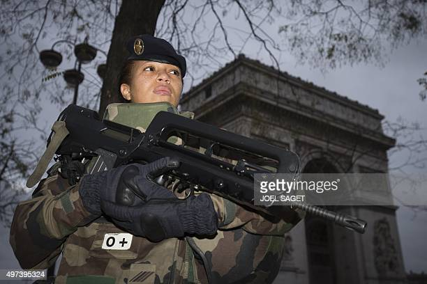 A French soldier enforcing the Vigipirate plan France's national security alert system patrols in front of The Arc de Triomphe on November 16 2015 in...