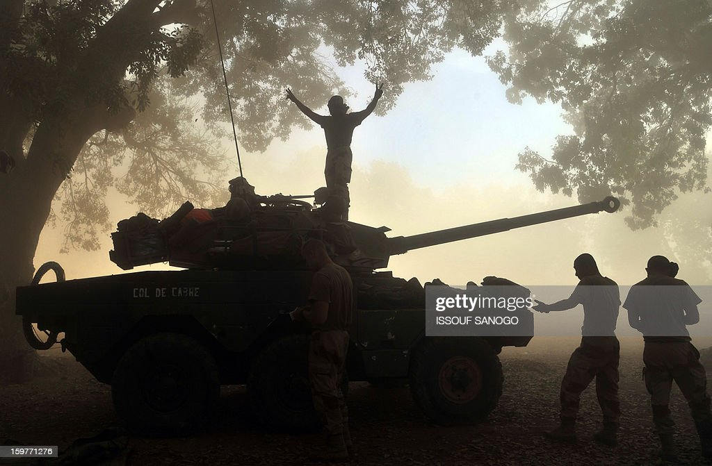 A French soldier flashes a victory sign as he stand atop a French tank in Niono, on January 20, 2013. French Defence Minister Jean-Yves Le Drian said today that the goal of France's military action in Mali was to retake control of the entire country from Islamist militants who have seized the north. 'The goal is the total reconquest of Mali. We will not leave any pockets' of resistance, Le Drian said on French television. AFP / PHOTO / ISSOUF SANOGO