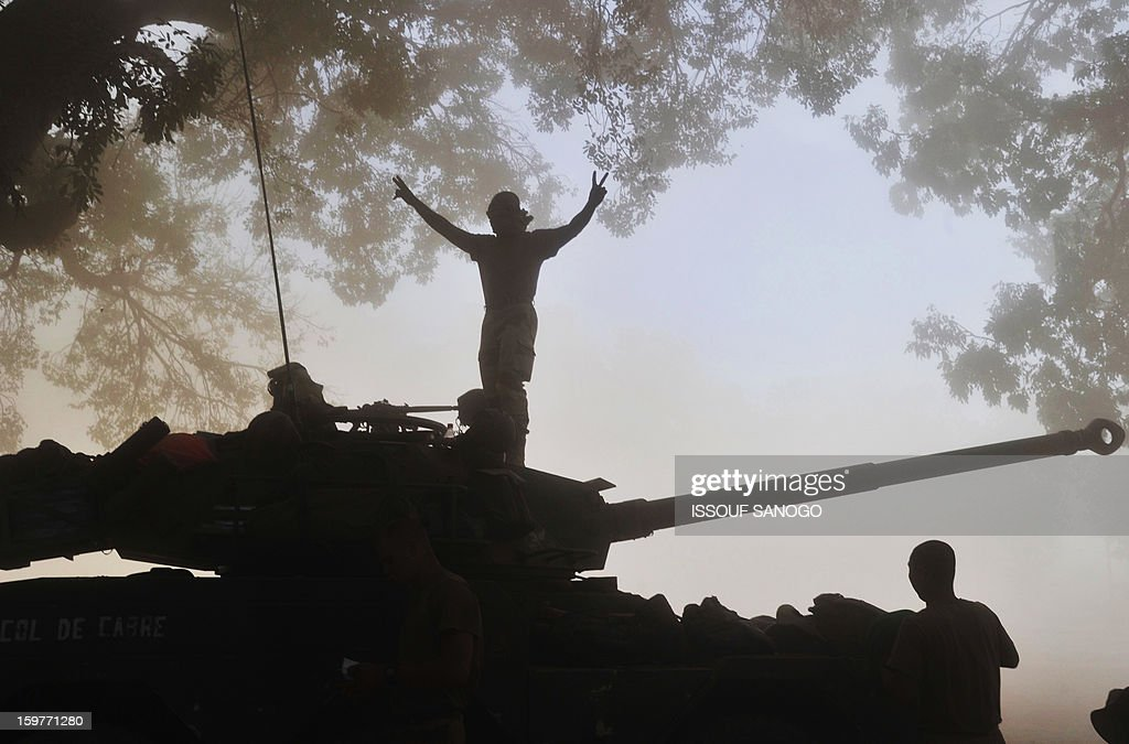A French soldier flashes a victory sign as he stand atop a French tank in Niono, on January 20, 2013. French Defence Minister Jean-Yves Le Drian said today that the goal of France's military action in Mali was to retake control of the entire country from Islamist militants who have seized the north. 'The goal is the total reconquest of Mali. We will not leave any pockets' of resistance, Le Drian said on French television. AFP / PHOTO / ISSOUF