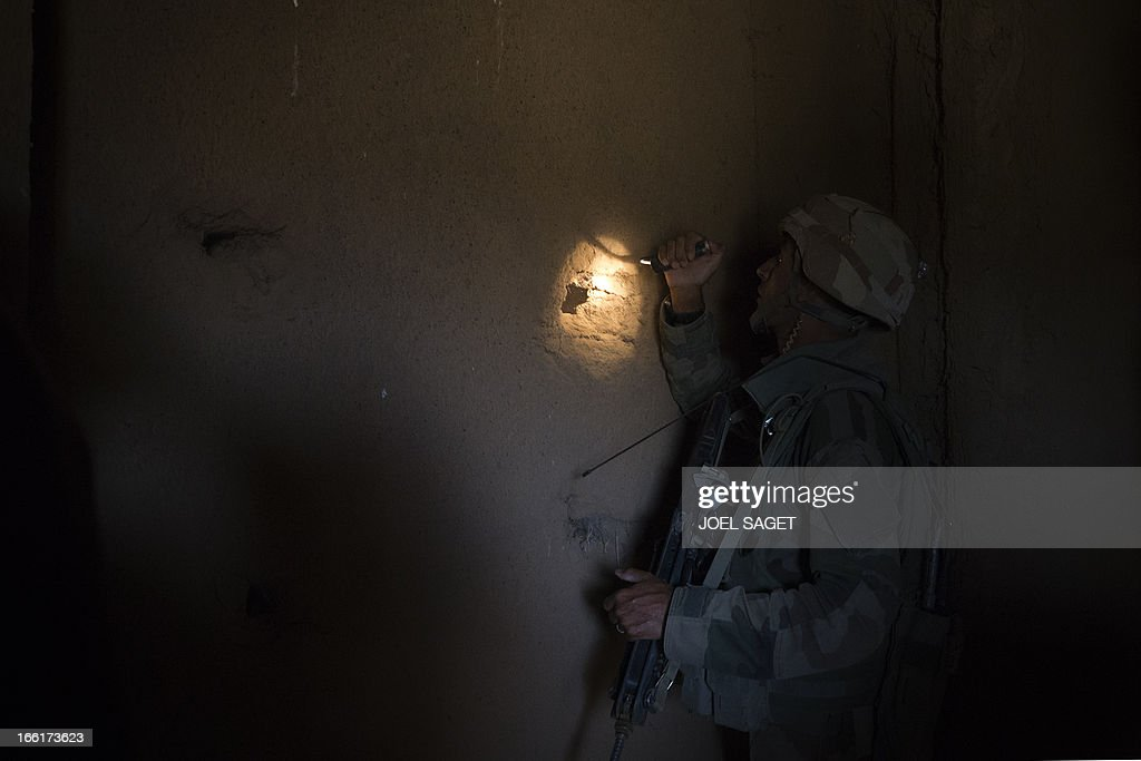 A French soldier from the 126th Infantry Regiment (RI) looks into a house 105 kms north of the northeastern Malian city of Gao on April 9, 2013 during day two of Operation Gustav, a hunt for Islamist fighters in a valley in northern Mali and one of France's largest military operations during its three-month intervention in its former colony. Operation Gustav comes with France preparing to withdraw three-quarters of the 4,000 troops it deployed in January to block a feared advance on the Malian capital Bamako by Al Qaeda-linked insurgents. AFP PHOTO / JOEL SAGET