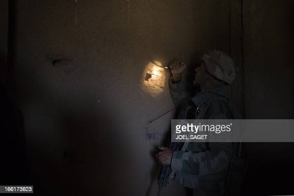 A French soldier from the 126th Infantry Regiment looks into a house 105 kms north of the northeastern Malian city of Gao on April 9 2013 during day...