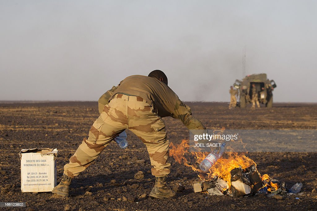 A French soldier from the 126th Regiment Infantery burns rubbish on April 8, 2013 some 105 kilometers North of Gao. A French force of 1,000 soldiers in a major offensive has swept a valley thought to be a logistics base for Al-Qaeda-linked Islamists near the Malian city of Gao. Operation Gustav, one of France's largest actions since its intervention against insurgents in January, will involve dozens of tanks, helicopters, drones and airplanes, said General Bernard Barrera, commander of the French land forces in Mali. AFP PHOTO / JOEL SAGET