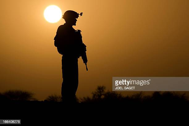 A French soldier from the 92 RI stands at sunset on April 7 2013 some 105 kilometers North of Gao during the Gustav operation in Mali Operation...