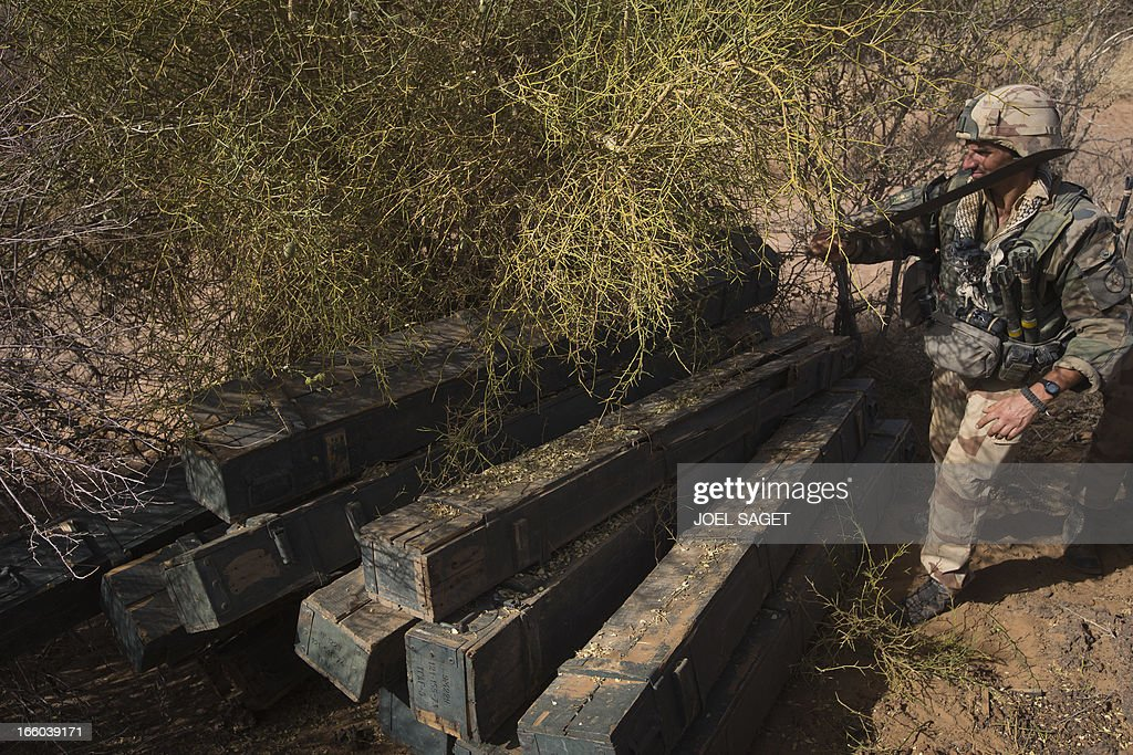A French soldier from the 92nd Infantery Regiment stands on April 7, 2013 near boxes containing 340 Chinese rockets allegedly belonging to Mujao forces, found some 105 kilometers North of Gao. A French force of 1,000 soldiers has begun a sweep of a river valley thought to be a logistics base for armed Islamists near the Malian city of Gao, an AFP journalist accompanying the mission said. Operation Gustav, one of France's largest actions since its intervention against insurgents in January, will involve dozens of tanks, helicopters, drones and airplanes, said General Bernard Barrera, commander of the French land forces in Mali. AFP PHOTO / JOEL SAGET