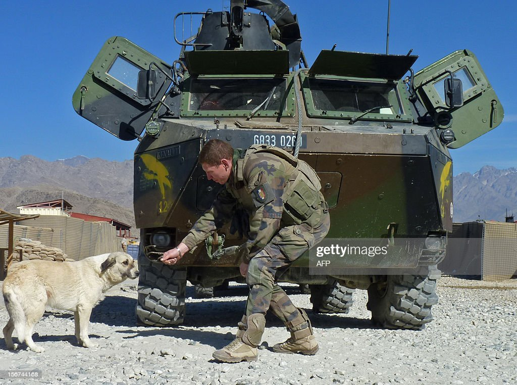 A French soldier gestures to a dog as he and his comrades prepare to depart for Kabul following a handover ceremony at the French military Camp Nijrab in Nijrab district of Kapisa province on November 20, 2012. France ended its combat mission in Afghanistan November 20, withdrawing troops from a strategic province northeast of Kabul as part of a quickened departure from the war-torn country. Paris says all French combat soldiers will leave the country next month, two years before allied nations contributing to the 100,000-strong International Security Assistance Force (ISAF) led by the United States are due to depart. AFP PHOTO/Joris Fioriti