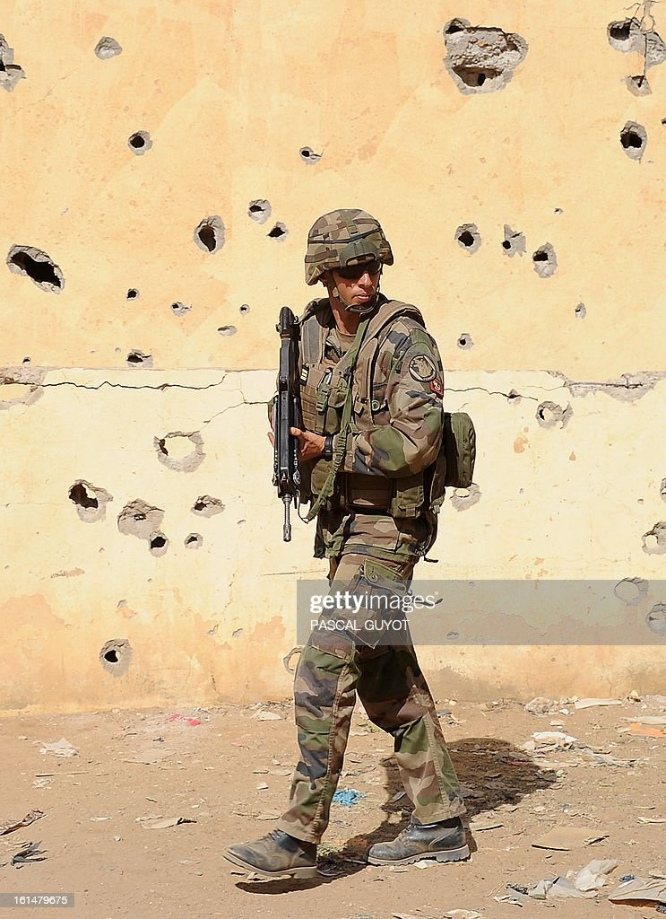 A French soldier holding a FAMAS F1 assault rifle patrols next to the central police station, on February 11, 2013 in Gao, one day after Islamist gunmen battled French and Malian troops. A French attack helicopter destroyed the central police station in Gao in a pre-dawn assault, after rebels from the Movement for Oneness and Jihad in West Africa (MUJAO) hiding in the building opened fire on Malian troops Sunday, sparking an hours-long street battle.