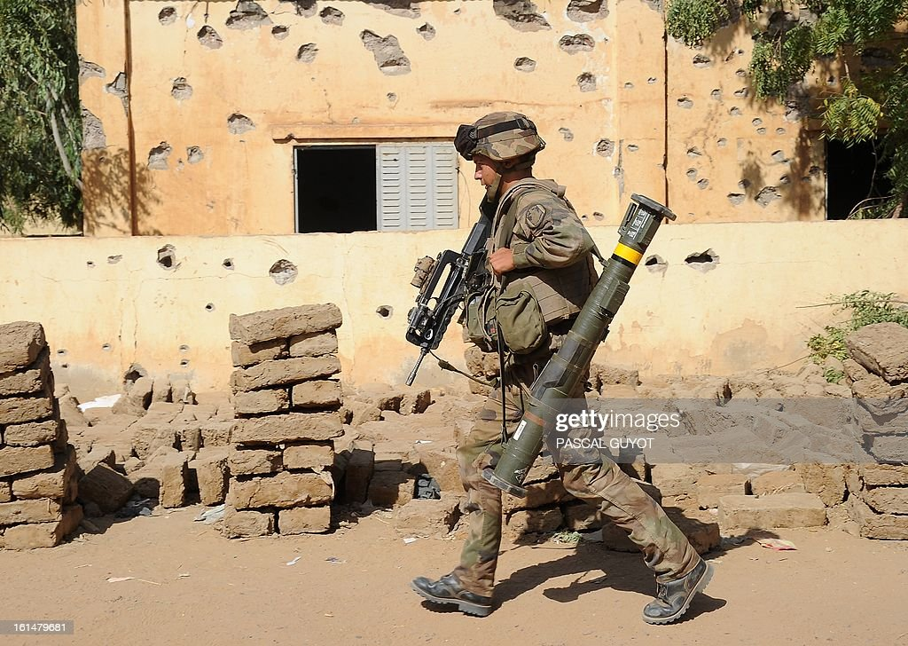 A French soldier holding a FAMAS-F1 assault rifle and a ABL (light anti-tank rocket launcher) patrols next to the central police station, on February 11, 2013 in Gao, one day after Islamist gunmen battled French and Malian troops. A French attack helicopter destroyed the central police station in Gao in a pre-dawn assault, after rebels from the Movement for Oneness and Jihad in West Africa (MUJAO) hiding in the building opened fire on Malian troops Sunday, sparking an hours-long street battle. AFP PHOTO / PASCAL GUYOT