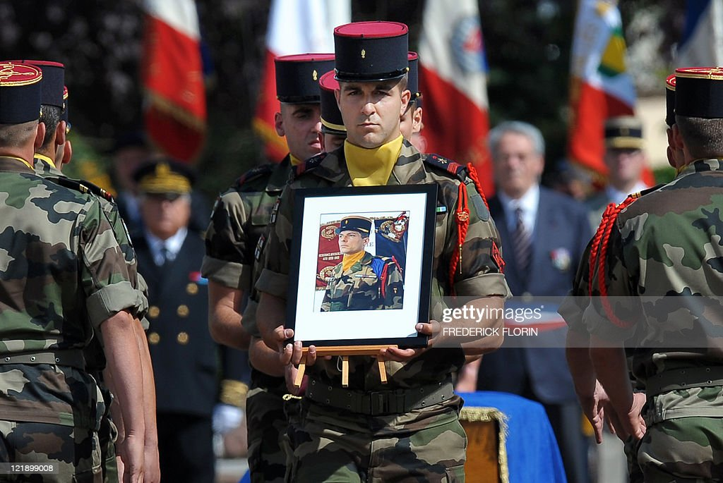 A French soldier holds a picture of French lieutenant Camille Levrel, on August 19, 2011 in Colmar, eastern France, during his funeral ceremony. Levrel, a 36-year-old officer who had also served in Kosovo and Chad, was shot dead in the northeastern Afghanistan region of Kapisa on August 14, 2011. The lieutenant's death, which took place during a support mission for the national Afghan forces, brings to 74 the number of French soldiers killed in Afghanistan since 2001