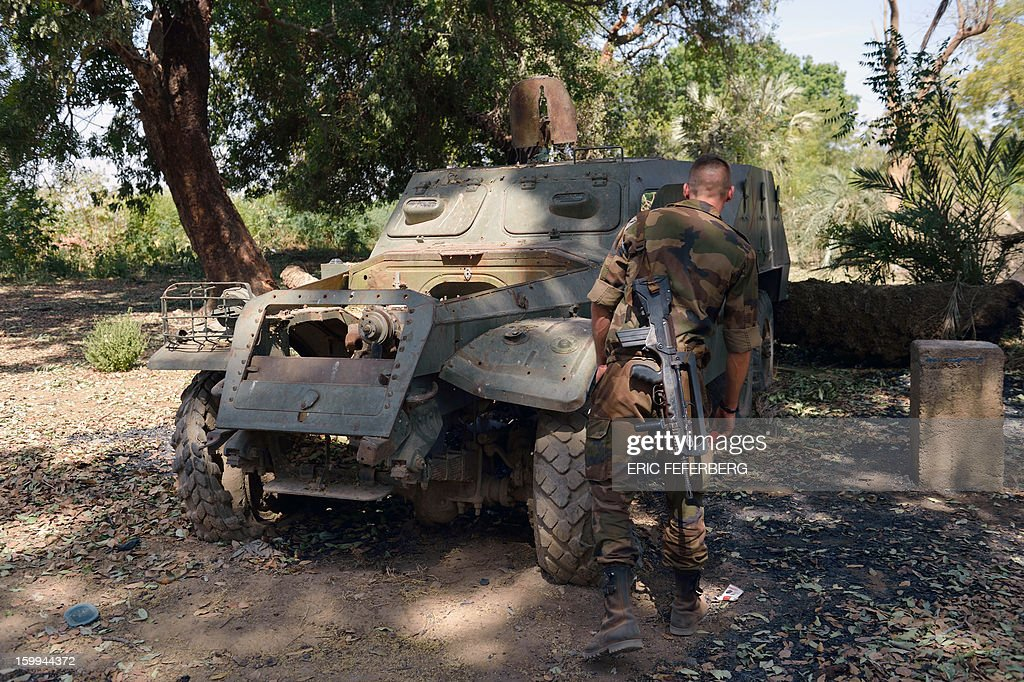 A French soldier inspects a Malian armoured vehicle on January 23, 2013 in the Malian barracks that was occupied by Islamists in Diabaly (400km north of the capital Bamako), before a French air strike destroyed it. French soldiers destroyed the munitions that belonged to the Islamists to secure the town.