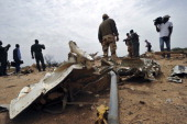 A French soldier looks at debris of the Air Algerie Flight AH 5017 as he stands at the crash site surrounded by journalists and representatives of...
