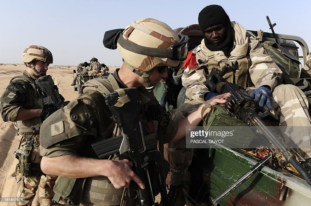 A French soldier (L) looks at the weapon of a Malian soldier as they enter Bourem, northen Mali on February 17, 2013. Leaders in Africa's Sahel region called on Saturday for further efforts to support Mali as they announced new funds to back a West African force in the country. A French-led military intervention launched on January 11 has driven the Islamist rebels in Mali from the towns they controlled, but concerns remain over stability amid suicide attacks and guerrilla fighting. GUYOT