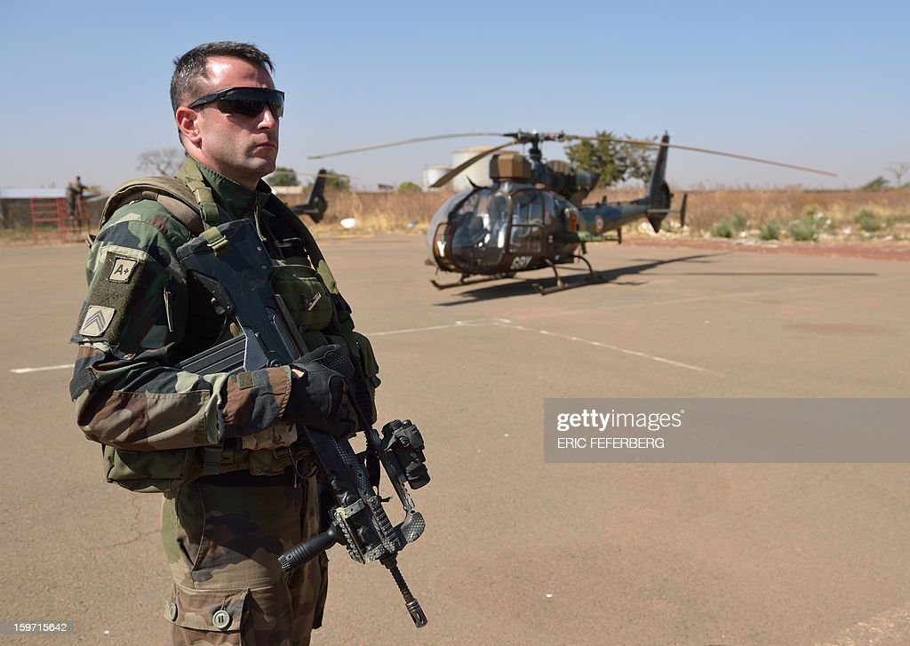 A French soldier of the 5th Combat Helicopter Regiment (RHC) stands guard stands near a Gazelle helicopter on January 19, 2013 at the 101st airbase near Bamako. French Defense Minister Jean-Yves Le Drian said on January 19 that France now had 2,000 troops on the ground in Mali as part of a drive against Islamist militants holding the north of the country.
