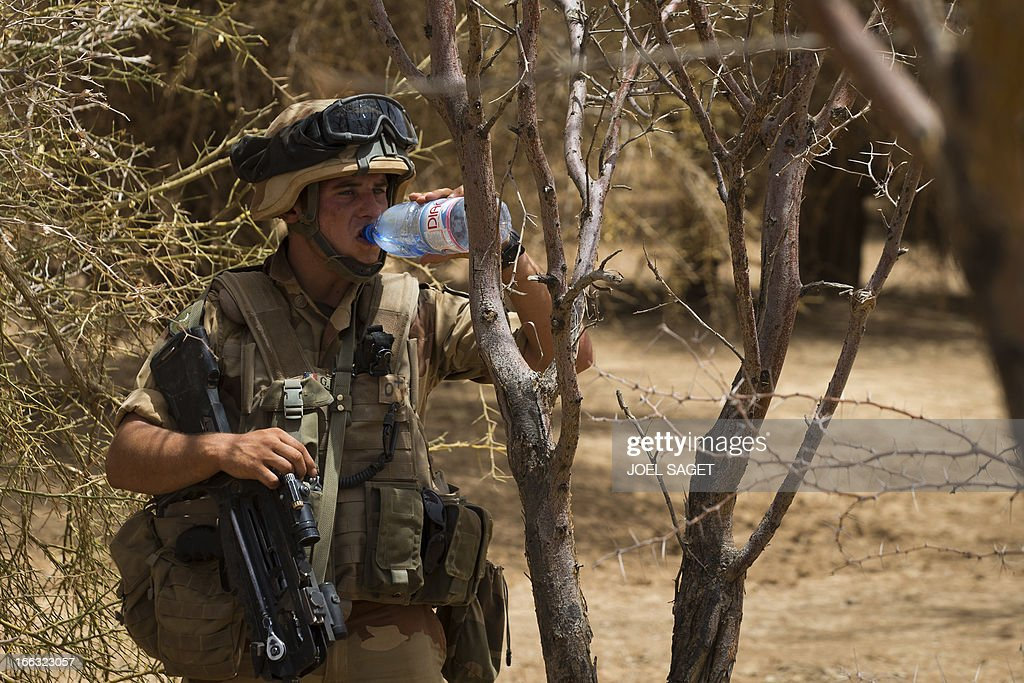 A French soldier of the 92nd Infantery Regiment drinks water as he takes part on April 10, 2013, 105 kms north of the northeastern Malian city of Gao, in day three of Operation Gustav, a hunt for Islamist fighters in a valley in northern Mali and one of France's largest military operations during its three-month intervention in its former colony. Operation Gustav comes with France preparing to withdraw three-quarters of the 4,000 troops it deployed in January to block a feared advance on the Malian capital Bamako by Al Qaeda-linked insurgents.