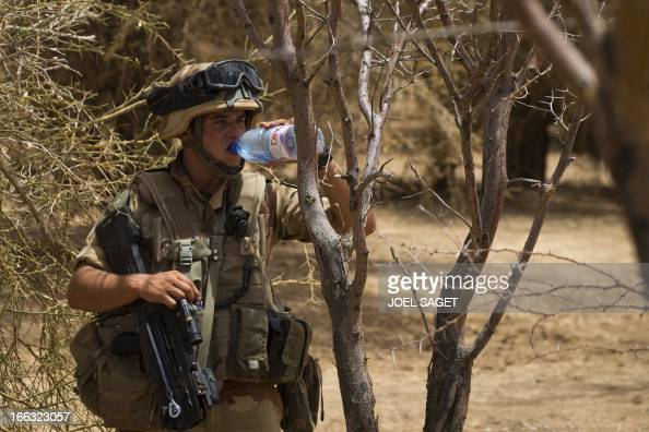 A French soldier of the 92nd Infantery Regiment drinks water as he takes part on April 10 105 kms north of the northeastern Malian city of Gao in day...