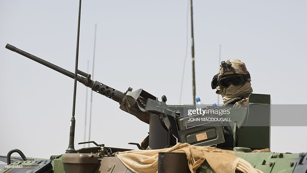 A French soldier of the 92nd Infantry Regiment (92eme R.I) mans a machine gun on an armoured personnel carrier (VAB) in the village of Amakouladji north of Gao on March 10, 2013, as a French civilian/military operation to assess the needs of the local population there is underway.