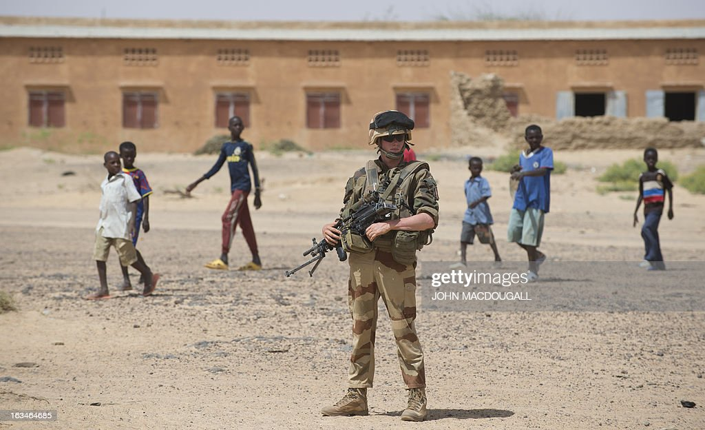 A French soldier of the 92nd Infantry Regiment (92eme R.I) secures the area in the village of Amakouladji north of Gao on March 10, 2013, as a French civilian/military operation to assess the needs of the local population there is underway. AFP PHOTO / JOHN MACDOUGALL