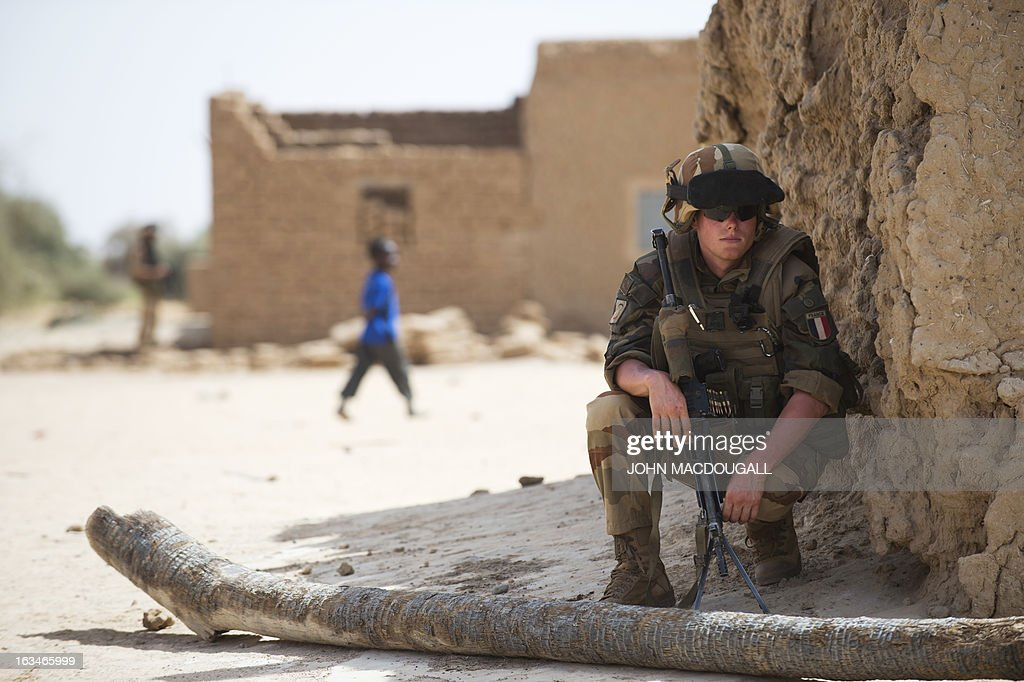 A French soldier of the 92nd Infantry Regiment (92eme R.I) secures the area in the village of Amakouladji north of Gao March 10, 2013, as a French civilian/military operation to assess the needs of the local population there is underway. AFP PHOTO / JOHN MACDOUGALL