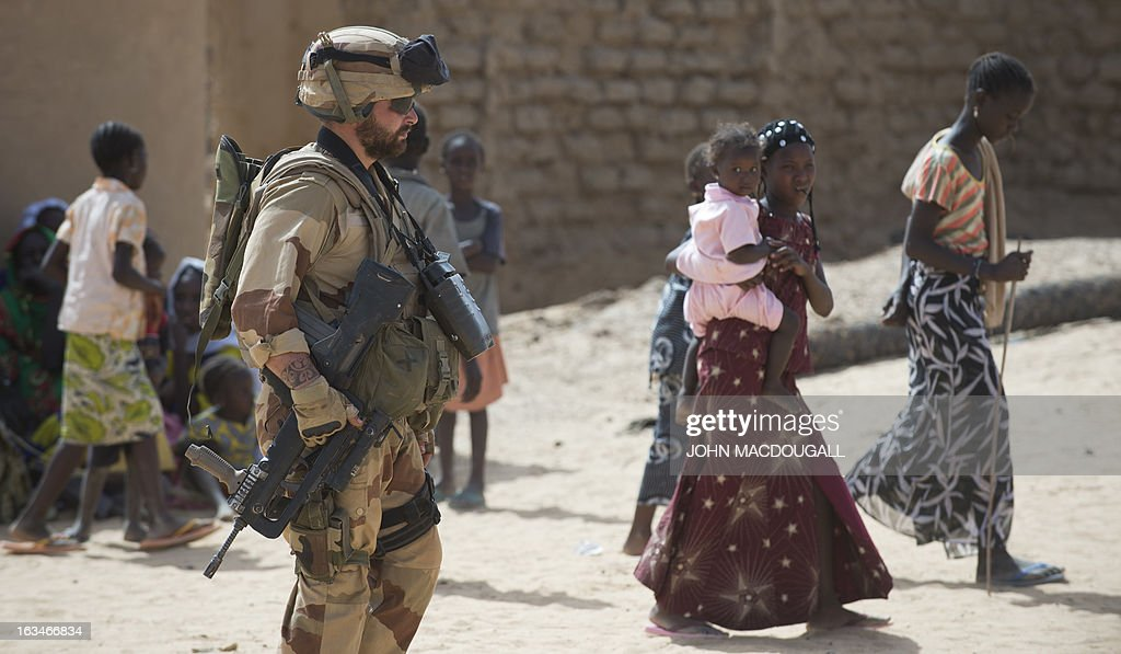 A French soldier of the 92nd Infantry Regiment (92eme R.I) secures the area in the village of Amakouladji, north of Gao, on March 10, 2013, to assess the needs of the local population there. AFP PHOTO / JOHN MACDOUGALL