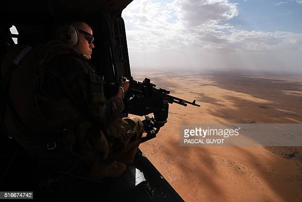 A French soldier of the operation Barkhane an antiterrorist mission in Sahel patrols as a tiger helicopter operates a tactical flight on March 12...
