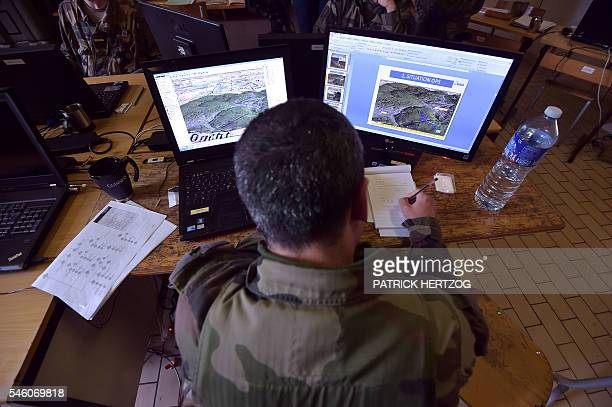 French soldier of the Second Hussar Regiment analyses on a computer observations and informations as he takes notes at a base camp in Bitche eastern...