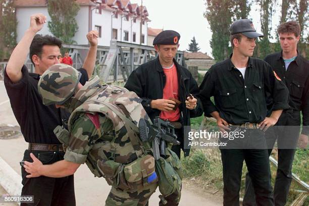 A French soldier part of NATOled KFOR troops check Kosovo Liberation Army fighters 21 June 1999 in Vuctirn north of Pristina The KLA signed a...