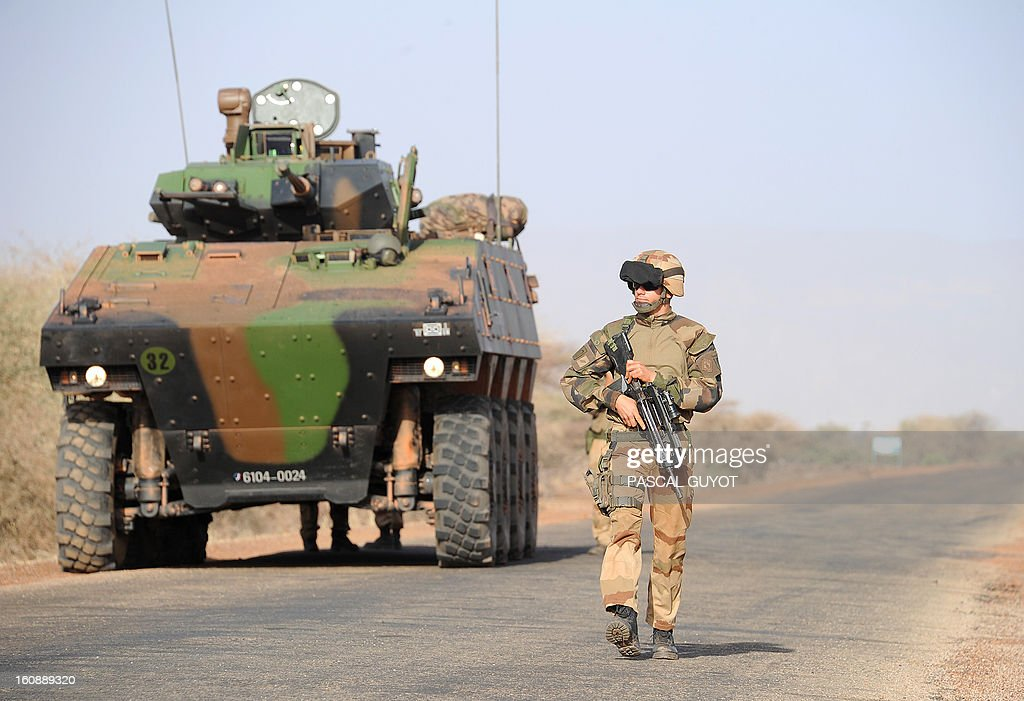 A French soldier patrols as a convoy of French army vehicules heads toward Gao on February 7, 2013 on the road from Gossi. Four Malian civilians were killed by a landmine in territory reclaimed from Islamist rebels, police said as France mulled handing over its four-week-old intervention to UN peacekeepers.