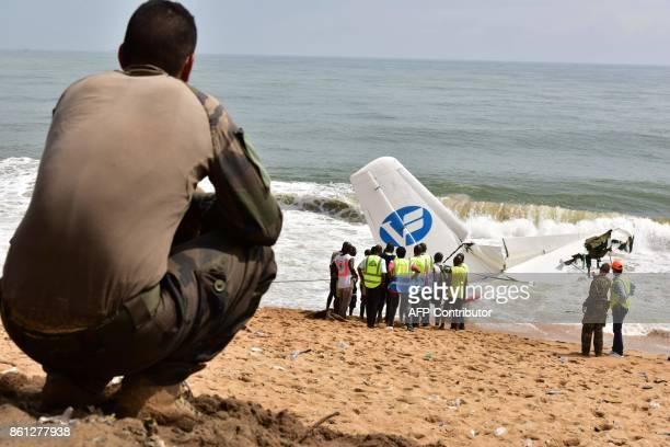 A French soldier squats on the beach of PortBouet in Abidjan near the wreckage of a cargo plane that crashed off Ivory Coast killing four on October...