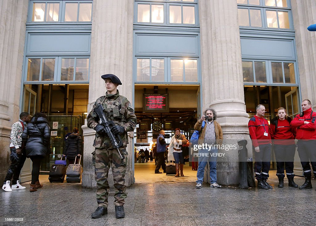 A French soldier stand in front of Gare du Nord railway station in Paris on December 21, 2012 as part of France's national security alert system 'Plan Vigipirate' which is reinforced for the end of the year celebrations. At right, members of the French Securite Civile (Civil defence).