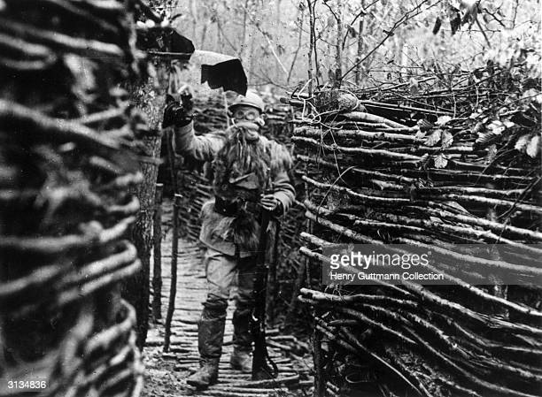 French soldier standing in a trench wearing a gas mask and makeshift winter uniform