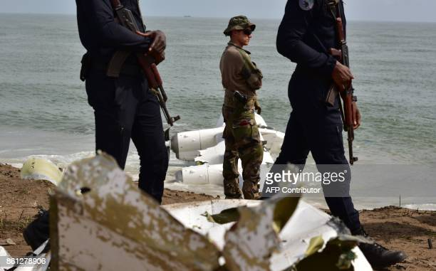 A French soldier stands as Ivory Coast's gendarmes walk on the beach of PortBouet in Abidjan near the wreckage of a cargo plane that crashed off...