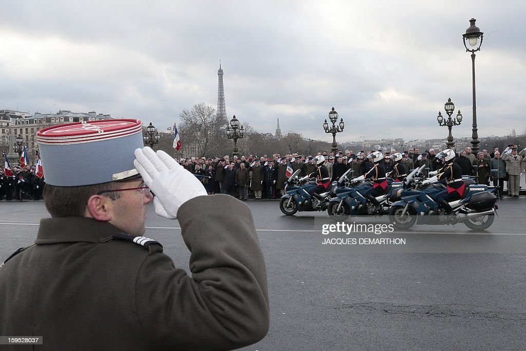 A French soldier stands at attention as the cortege following the hearse carrying the coffin of French air force lieutenant Damien Boiteux, killed on January 11, 2013 during French military operation 'Serval' in Mali, crosses the Alexandre III bridge in Paris, on January 15, 2013. French pilot Damien Boiteux was killed during a helicopter raid launched to support Mali ground troops in the battle for the key town of Kona, and to prevent Islamist groups controlling northern Mali from advancing toward the capital Bamako.